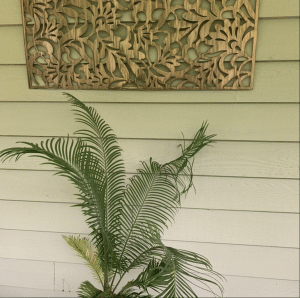 Metal Art Wall Decor rectangular Screen with Floral pattern and a wood grain copper patina. This photo showcases the metal screen outdoor on a patio next to a plant.
