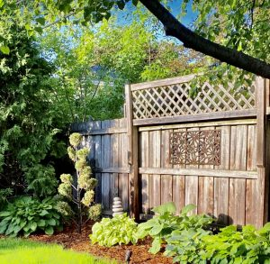 Metal Art Wall Decor rectangular Screen with Daisy pattern and a wood grain copper patina. This photo showcases the metal screen outdoor on a wooden fence.