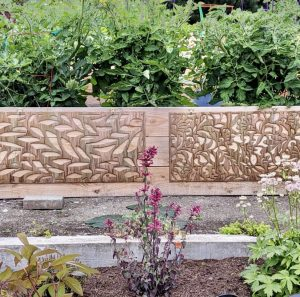 Two pieces of Metal Art Wall Decor rectangular Screens with the Fern and Floral pattern and a wood grain copper patina. This photo shows the screens side by side leaning on a wall in the garden with flowers.